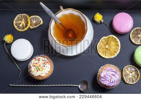 Tea In A Cup And Saucer, Dried Yellow Roses, Cake On A Black Background. Afternoon Tea.