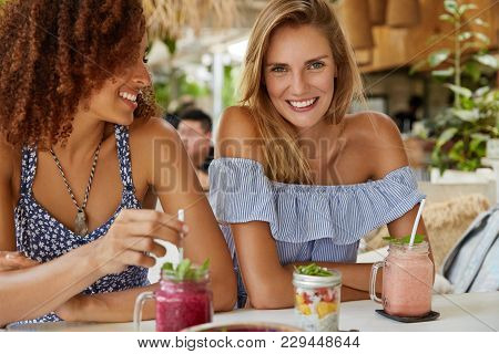 Pleased Female Lesbians Have Date At Cafe, Drink Fresh Fruit Cocktails, Discuss Something With Cheer