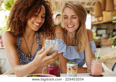 Happy Young Women Watch Funny Video In Internet On Smart Phone, Sit Together Against Cafe Interior,