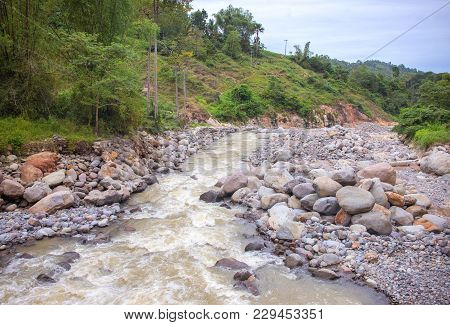 Tropical River Panorama. Tropical Landscape. Fresh River In Stone Riverbed. Tropical Nature In Rain
