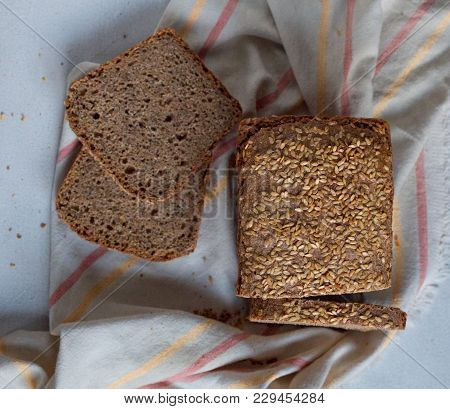 A View Of A Loaf Of Rye Bread On A Wooden Table. Loaves Of Rye Bread Lie Next To Each Other. Sliced