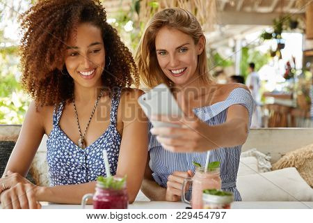 Portrait Of Good Looking Females Make Selfie With Smart Phone, Sit Together At Outdoor Cafe, Spend S