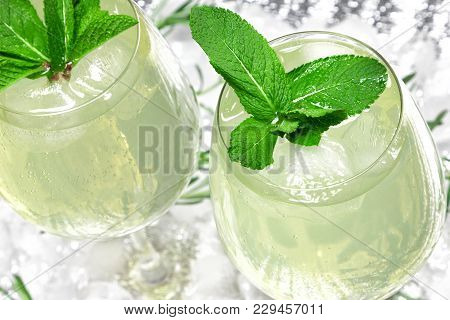 Refreshing Summer Drink With Mint In Large Wine Glasses Surrounded By Ice Cubes. Cold Mojito. Ice Le