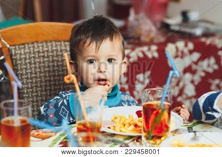 Child Eating Fries With Your Hands At A Birthday Party Eagerly In A Blue Sweater