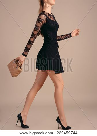 A Tall, Slender Girl In A Little Black Dress With Short Fashion Handbags Takes A Step