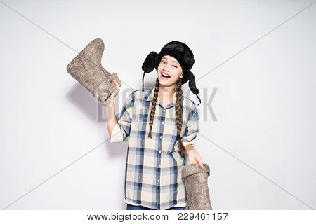 Laughing Beautiful Russian Girl Holding Warm Winter Felt Boots, Fur Hat On Her Head