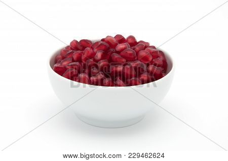 Full Cup Of Seeds Of A Pomegranate On A White Background.