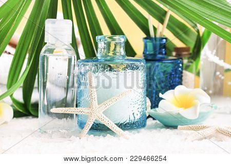 Light Blue Glass Jar Of Sea Salt With Starfish Decor, Bottle Of Facial Mineral Lotion, Palm Leaf. Be