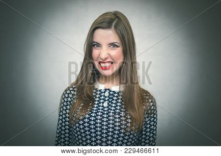 Angry Aggressive Woman Isolated On Gray Background. Girl In Bad Mood.