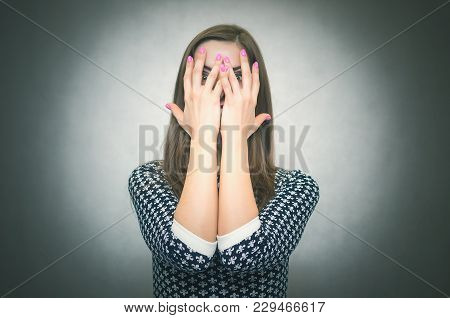 Angry Aggressive Woman In Shock Is Shouting And Close Her Face By Her Hands Isolated On Gray Backgro
