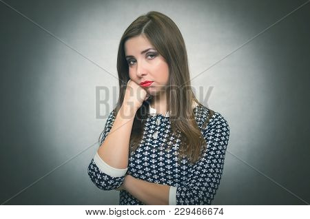 Pensive Wistful Woman Is Wondering And Thinking Isolated On Gray Background. Disappointed Girl.