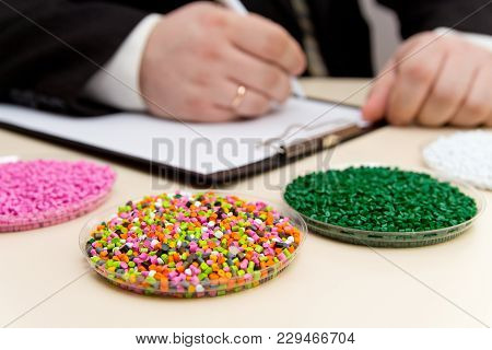 Businessman Inspects Plastic Pellets For Industry. Plastic Raw Materials In Granules . Polymer, Plas