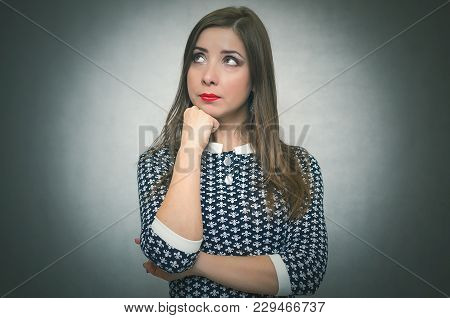 Pensive Wistful Woman Is Wondering And Thinking Isolated On Gray Background.