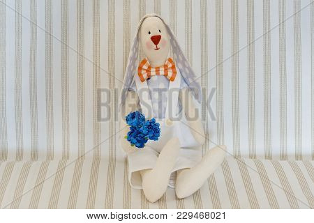 Easter Bunny Rabbit, Hand Maid Toy. On A Light Striped Background.