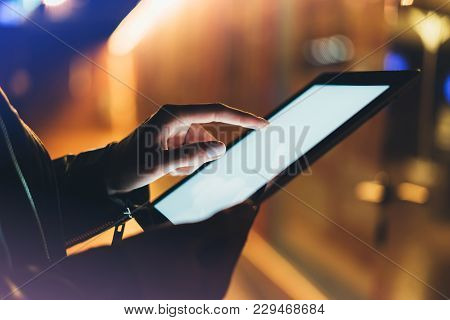 Girl Holding In Hands On Blank Clean Screen Tablet On Background Glow Bokeh Lights In Night Atmosphe