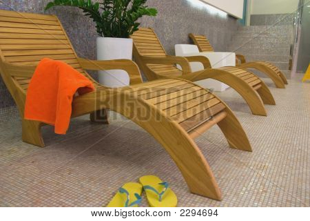 Sunbed With Orange Towel And Sandals, Plant Behind