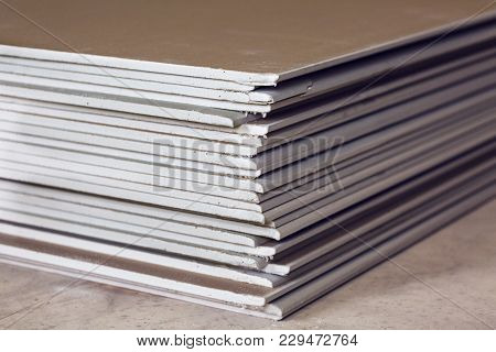 A Lot Of Sheets Of Plasterboard Or Drywall Close Up In An Apartment During On The Construction, Remo