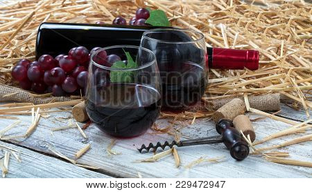 Close Up View Of Drinking Glasses Filled With Red Wine, Bottle And Grapes Plus Corkscrew With Straw