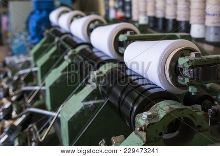 Big Spools With White Thread At Rewinding Machine At Knitting Shop View