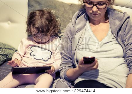 Baby Sits Near Her Mother And Uses A Digital Tablet. Two-year-old Child Looks Electronic Device At H