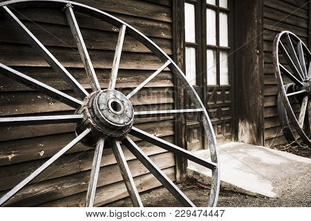 Wheels Of An Old Chariot Leaning Against The Wall Of A Wooden Made House