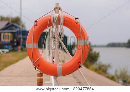 The Orange Lifebuoy Is Tied To A Fence On The River Pier. Frontal View. The Concept Of Life Saving,