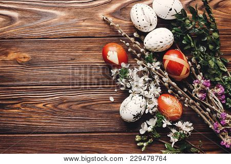 Stylish Easter Eggs With White Flowers And Buds On Wooden Background Flat Lay. Modern Eggs And Natur