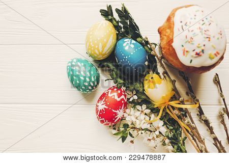 Stylish Easter Eggs And Easter Bread Cake And Flowers On Wooden Background Flat Lay. Modern Colorful