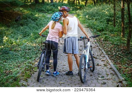 Loving Young People Met In The Park. Ride On Bicycles. The Concept Of Cycling And A Healthy Lifestyl