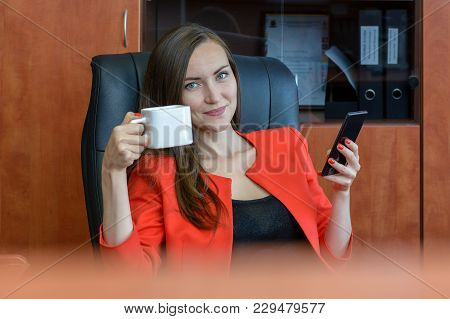 Portrait Of A Girl In A Red Business Suit Sitting Resting In A Chair, Drinking Tea And Using A Smart