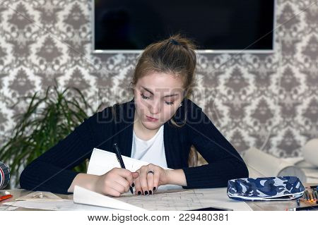 Frontal Portrait Of A Young Female Student Is Engaged At The Table Draws Sketches, Sketches, Plans,