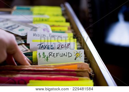 Tax Refund Tax Filing For 2018 Tax Time,hand In Filing Cabinet Looking For Receipts And Deductions O
