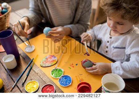 Portrait Of Adorable Little Boy Painting Easter Eggs While Making Decorations For Easter Holiday, Co