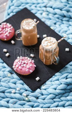 Pink Donut With Marshmallow And Hot Chocolate In Cup On Blue Merino Knit Blanket. Lights On Backgrou