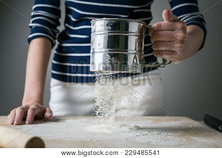 Women's Hands Sprinkle A Wooden Board With White Flour For Cooking. Dynamically Frozen Flour In Flig