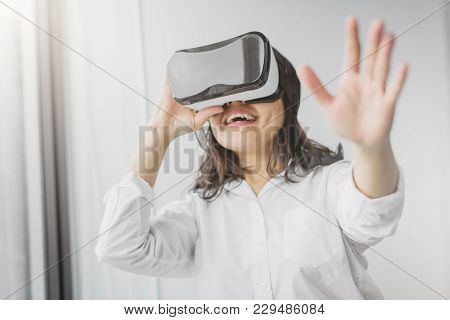 Shot Of Excited Woman Having Fun While Wearing Vr Headset In Living Room. Focused On Vr Headset