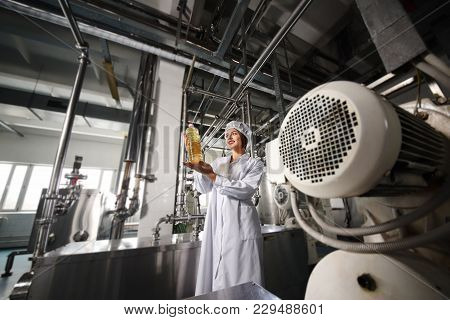 A Beautiful Young Girl In White Uniform Or A Working Dressing Gown With A Bottle Of Sunflower Oil In