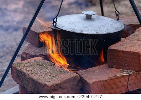 Fish Soup Boils In A Cauldron On An Open Fire. Soup In A Pot On A Fire, Picnic In Nature.