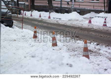 Red Plastic Barrier On The Road In Winter.