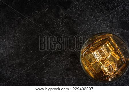 Whisky Or Whiskey Or Bourbon With Ice On Dark Stone Table Top View