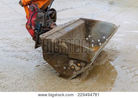 Excavator Closeup And Wet Sand, By Work Pause