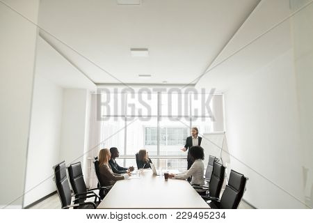 Successful Caucasian Businessman Gives Presentation Working With Flip Chart In Meeting Conference Ro