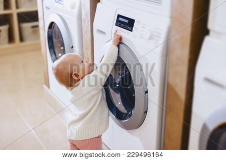 The Girl Is Playing With A Washing Machine
