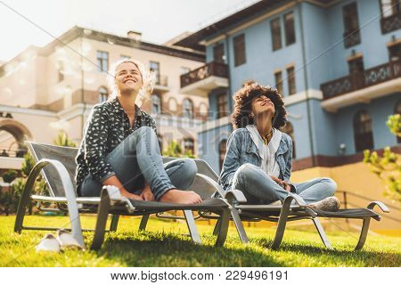 Black And Caucasian Female Friends On Daybeds Are Sitting Outdoors On The Lawn And Enjoying Bright S