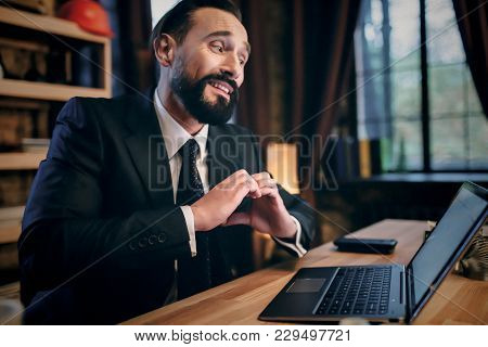 Satisfied With Work Done. Happy Young Man Working On Laptop While Sitting At His Working Place In Of