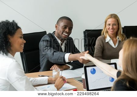 Black Satisfied Businessman Handshaking White Businesswoman Concluding Contract, Smiling Happy Afric