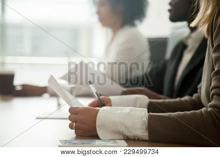 Diverse Attentive People Sitting At Conference Table Holding Documents At Group Meeting Briefing, Af