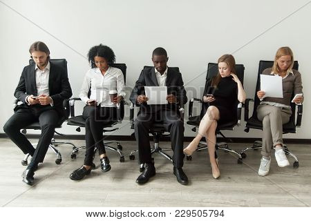 Nervous Applicants Preparing For Employment Interview Sitting On Chairs In Queue Row Line, African A