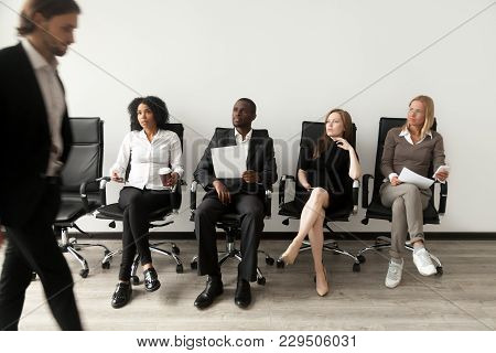 Rivalry at job interview concept, applicant walking in room while envious curious multiracial people sitting in row looking at rival waiting for result, winner and loser, jealous of other success poster