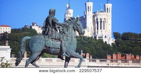 Famous Statue Of Louis Xiv And Basilique Of Notre Dame De Fourviere On A Background